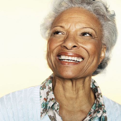 Older Chandler, AZ woman smiling about her dental implants after successful sinus augmentation surgery.