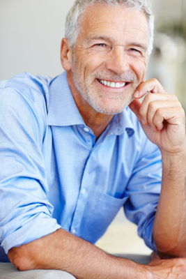 Older Chandler, AZ man smiling about his dental implants after successful socket preservation surgery.